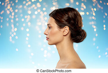beauty, bodycare and people concept - profile of beautiful young woman with bare shoulders over holidays lights on blue background