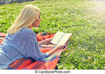 Profile of blonde girl read book on green grass