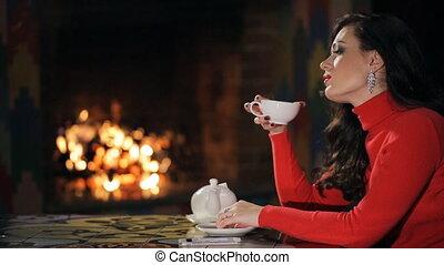 profile of brunette in red sweater, drinking tea indoor.