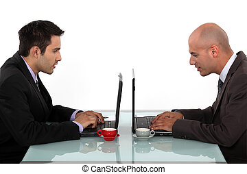 Profile of businessmen working at their laptops
