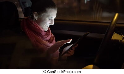 Profile of emotional girl sitting in the car and using tablet. 4K