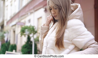 Profile of fashionable girl posing to camera in fur coat on the street 4K