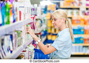 Profile of girl at the shop choosing cosmetics