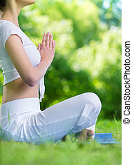 Profile of girl in lotus position prayer gesturing