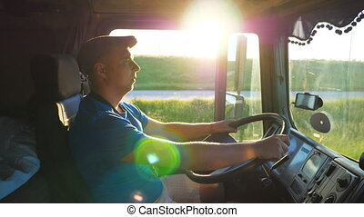 Profile of lorry driver riding through countryside at sunset...