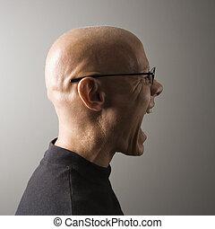 Profile of man screaming.