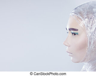 Profile of misterous pretty woman wrapped in cellophane looking forward standing on light grey background
