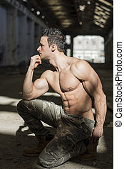 Profile of muscular shirtless young man in abandoned warehouse