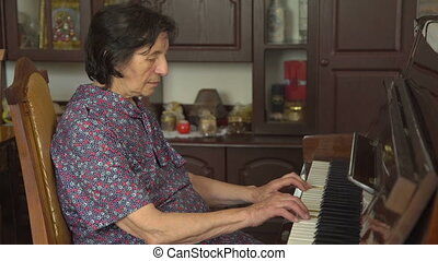 Profile of old woman is playing the piano at home