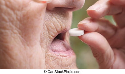 Profile of old woman taking a white pill to alleviate her health issues. Grandmother putting tablet in her mouth outdoor. Concept of healthcare and medicine. Side view Close up Slow motion