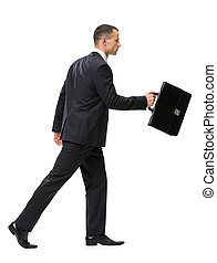Profile of walking with suitcase businessman