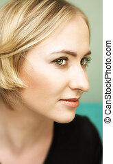 Profile of young blond woman with green eyes