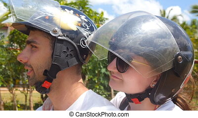 Profile of young couple in helmets riding a scooter along tropical country road. Smiling man and woman travel on motor bike during summer vacation. Happy pair taking selfie during trip. Close up