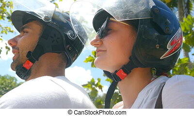 Profile of young couple in helmets riding a scooter along...