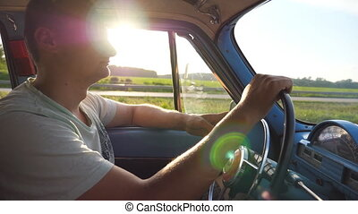Profile of young man holding hands on steering wheel and driving a retro car with sun flare at background. Caucasian guy traveling in a vintage vehicle at countryside. Side view Slow motion Close up