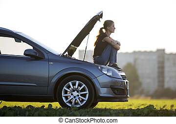 Profile of young slim attractive woman sitting on car with popped hood in green meadow waiting for help on clear sky copy space background. Transportation, vehicles problems and breakdowns concept.