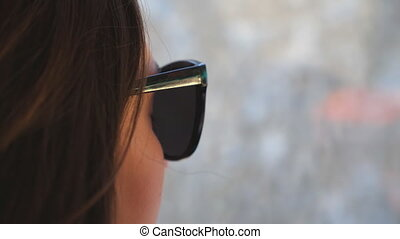 Profile of young woman traveling by bus and looking to window. Girl in sunglasses watching out the window during trip. Female tourist takes a autobus ride. Vacation or excursion concept. Close up