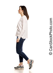Profile of young woman walking on white background