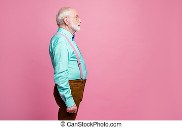 Profile photo of attractive grandpa looking empty space concentrated focused not smiling wear specs mint shirt suspenders bow tie pants isolated pink pastel color background