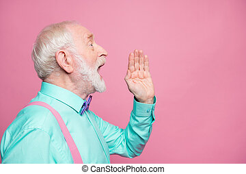 Profile photo of attractive grandpa looking empty space hand near open mouth yelling secret information people crowd wear mint shirt suspenders bow tie isolated pink pastel color background