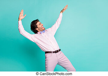 Profile photo of charming brunet curly hair clubber man wear pink shirt dancing stretching hands side looking empty space isolated teal color background