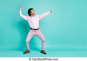 Profile photo of cheerful brunet curly hair clubber man wear pink shirt dancing stretching fists side looking empty space isolated teal color background