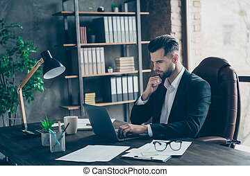 Profile photo of curious business brunet guy looking notebook table reading colleagues email letters analyzing reports wear blazer shirt suit sitting chair office indoors