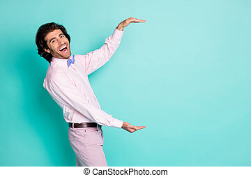 Profile photo of cute charming brunet wavy hair man dressed pink outfit measure empty space two hands isolated teal color background