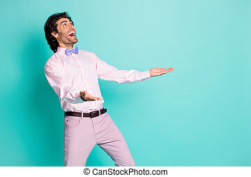 Profile photo of cute funny boyfriend wear pink outfit looking up empty space arms up open mouth isolated teal color background