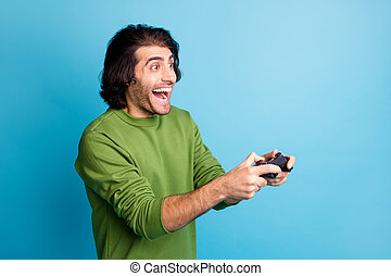 Profile photo of funny bearded guy hold gamepad open mouth wear green pullover isolated blue color background