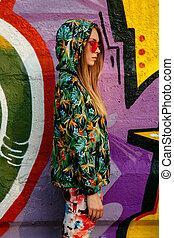 Profile picture of a stylish girl, standing near the wall with graffiti