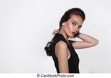 Profile portrait of a beautiful woman, dressed in black dress, with makeup, looking at camera, on a white background.