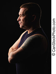 Profile portrait of a serious brutal man with tattoo