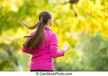 Profile portrait of a young attractive woman jogging in the autu