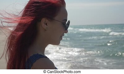 profile portrait of a young woman with red hair flying in the wind in sunglasses and with braces on her teeth against the background of the sea surf
