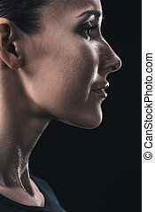 profile portrait of attractive young woman isolated on black.