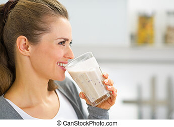 Profile portrait of happy young woman drinking fresh...