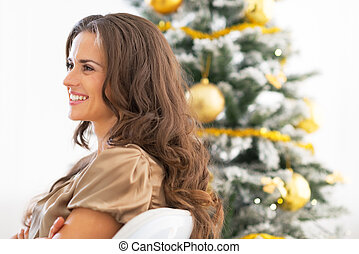 Profile portrait of happy young woman sitting near christmas tre