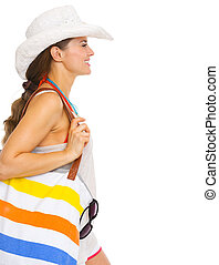 Profile portrait of happy young woman with beach bag looking on copy space