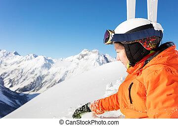 Profile portrait of teen girl in orange ski outfit