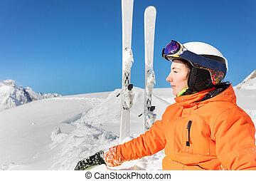 Profile portrait of teen girl in orange with ski