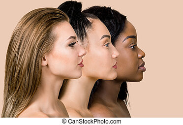 Profile portrait of three beautiful multicultural young women. Close up of faces of European, Asian and African women posing in studio over beige background. Ethnic skin types. Different ethnicity