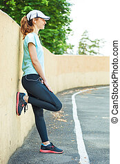 Profile portrait of young woman ready to start her morning running session.