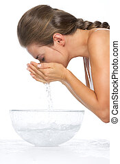 Profile portrait of young woman washing face in glass bowl with water