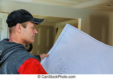 Profile shot of a bearded male architect working on blueprints sitting at his desk at the office copyspace building plans construction project engineer expert specialist qualified job occupation