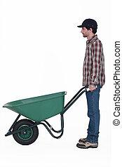 Profile shot of man stood with wheelbarrow