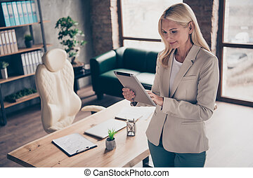 Profile side photo of focused charming middle aged woman entrepreneur use her tablet read start-up review project have briefing with her clients workshop wear jacket in office