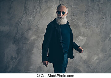 Profile side photo of handsome harsh masculine man in eyewear eyeglasses looking wearing coat black blazer jacket trousers isolated over gray background