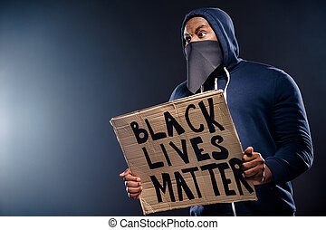 Profile side photo of shocked afro american guy hold banner impressed police, community injustice racism issues wear sweater jumper isolated over black color background