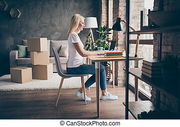 Profile side view of her she nice blonde confident successful cheerful woman sitting in chair using laptop selling buying things goods hu,an occupation modern loft brick industrial interior house flat